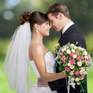 Bride and groom facing each other. The bride is in her white wedding dress and holding a bouquet of flowers.