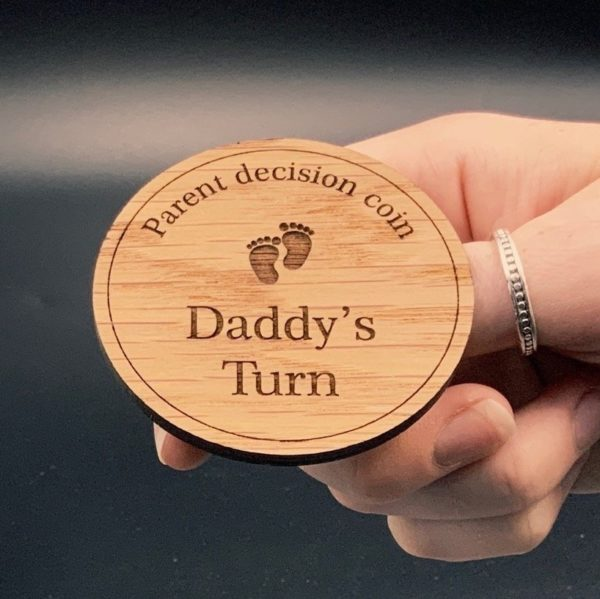 a novelty oak flip coin for new parents to decide whether it is mummy's or daddy's turn